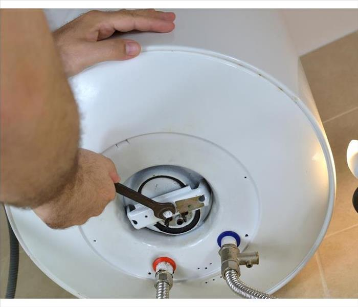Man's hands unscrewing a screw-nut on a water heater with a wrench on a boiler