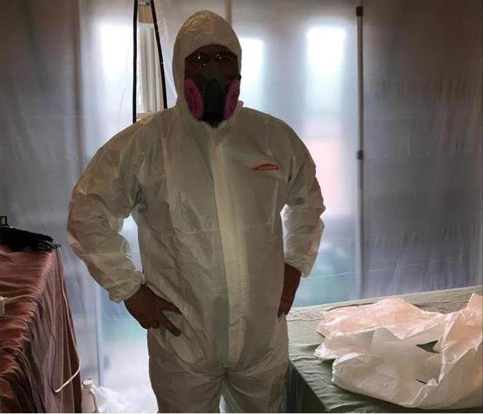 Technician wearing protective equipment while doing mold remediation