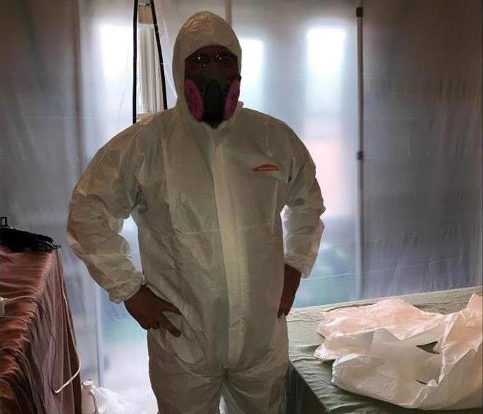 A mold technician wearing a white suit, goggles and a respirator mask