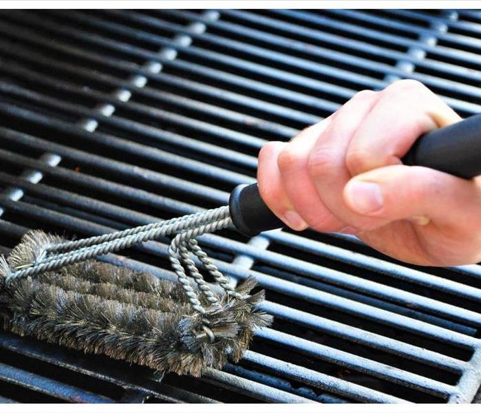 Cleaning a grill with a brush