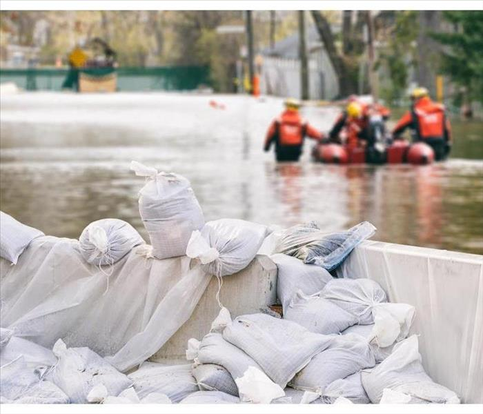 Flood Protection Sandbags with flooded homes in the background (Montage)